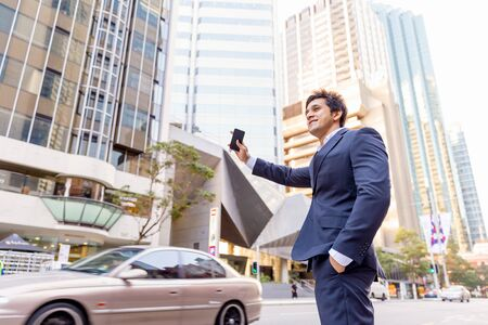 hailing: Businessman in suit catching taxi in city with mobile phone in his hands Stock Photo