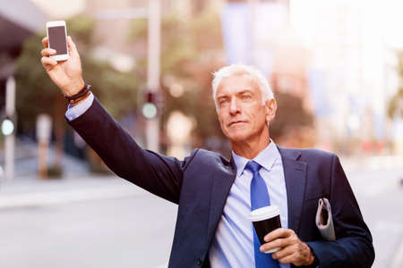 hailing: Businessman in suit catching taxi in city with cup of coffee in his hands