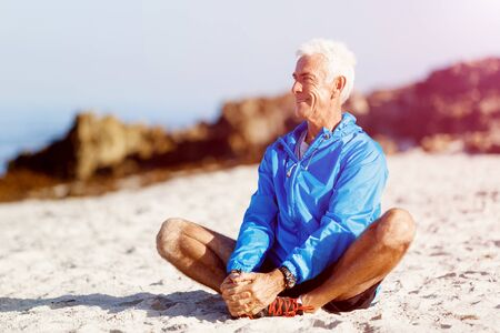sports wear: Man in sports wear sitting alone at the beach and having minute of rest Stock Photo