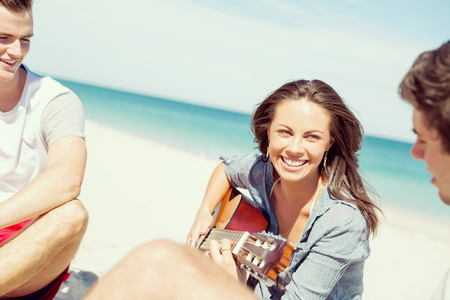 Beautiful young smiling woman playing guitar on beach