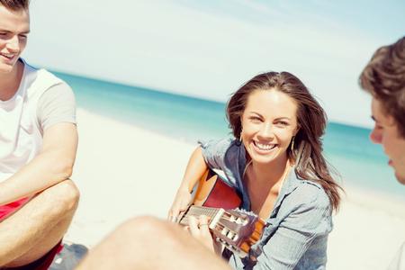 Beautiful young smiling woman playing guitar on beach