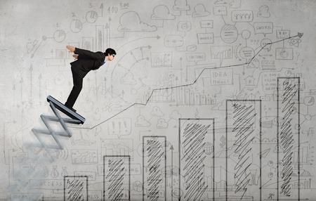 springboard: Businessman jumping on springboard as progress concept