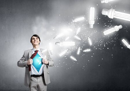powerful creativity: Young smiling businessman acting like super hero and tearing his shirt off