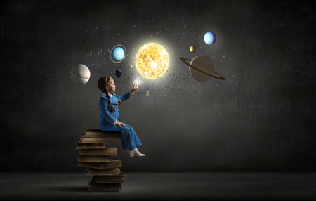 children learning: Little girl sitting on stack of books and touching planet