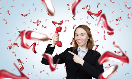 receiver: Portrait of young businesswoman with red phone receiver in hands Stock Photo
