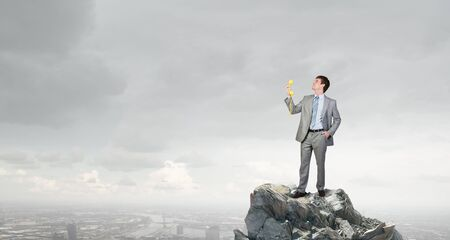 important phone call: Smiling businessman talking on yellow phone handset on rock top