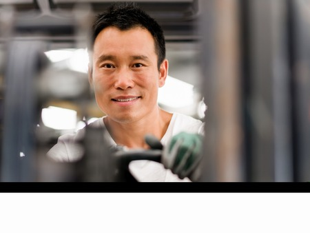 metalworker: portrait of asian worker in production plant working on the factory floor Stock Photo