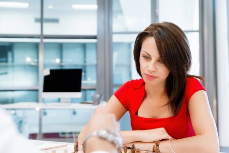 human intelligence: Business woman sitting in front of chess and planning Stock Photo