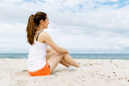 sports wear: Young woman in sports wear sitting alone at the beach and having minute of rest