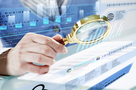 finance report: Close up of business person investigating infographs with magnifier