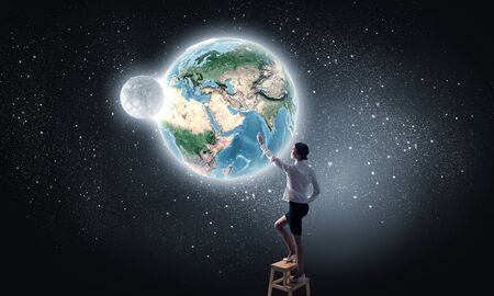 achieve: Businesswoman standing on chair and reaching Earth planet. Elements of this image are furnished by NASA Stock Photo