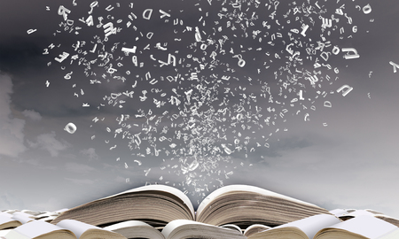 Geopend boek met tekens die uit pagina's vliegen