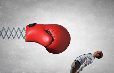 Jonge vastberaden zakenman vechten bokshandschoen op de lente Stockfoto