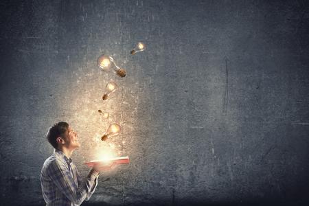 bombillo: Hombre joven que sostiene libro abierto con las bombillas de cristal brillante de volar