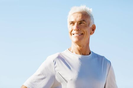 sports wear: Man standing on beach in sports wear looking fit and happy