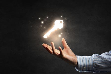 Úspěch: Zblízka podnikatel ruka ukazuje klíčem k úspěchu