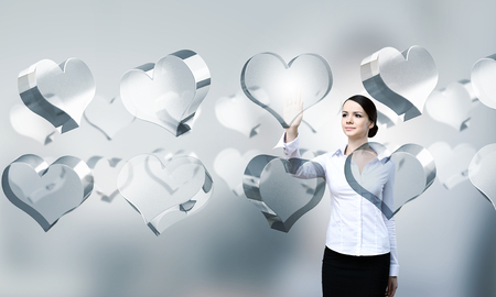 high tech: Attractive businesswoman touching high tech heart icon Stock Photo