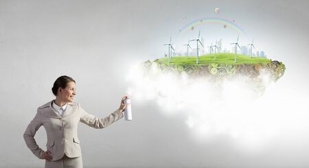 Young businesswoman spraying eco concept from aerosol balloon Stock Photo