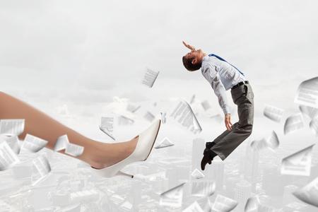 dismissal: Big businesswoman foot kicking tiny businessman as dismissal concept Stock Photo