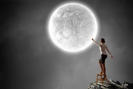 moon chair: Businesswoman standing on chair and reaching hand to touch moon
