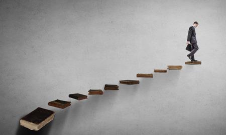 Businessman walking on career ladder made of books