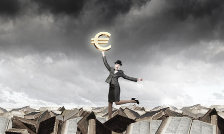 bowler: Young businesswoman in suit and bowler hat catching euro symbol Stock Photo