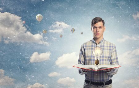 broaden: Young man holding opened book and glass glowing bulb on pages