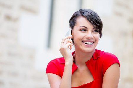 phone professional: Portrait of beautiful business woman in red dress holding her mobile
