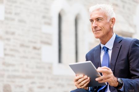 hombres maduros: Hombre de negocios mayor que sostiene touchpad aire libre
