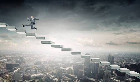 rise to the top: Young businessman running up on staircase representing success concept