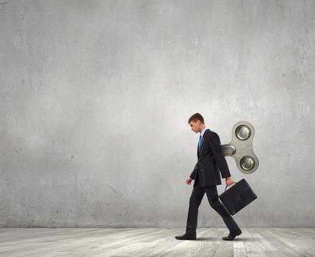 風が背中にキーを歩く若いビジネスマン