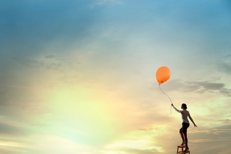 reaching hand: Businesswoman standing on chair and reaching hand with balloon