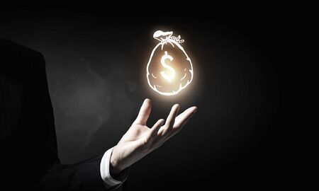 business savings: Hand of businessman holding money bag symbol on dark background