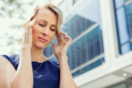 concentrate on: Businesswoman standing in street and trying to concentrate Stock Photo