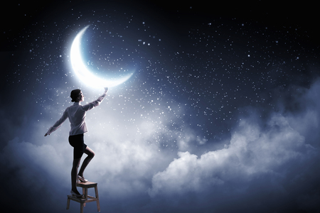 moon chair: Young woman standing on chair and reaching moon
