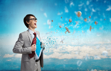 powerful creativity: Young businessman acting like super hero and tearing his shirt off Stock Photo