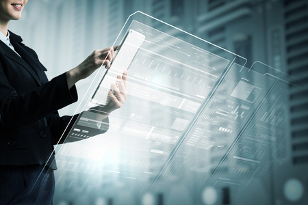 Geschäftsfrau mit Tablette-PC gegen High-Tech-Hintergrund
