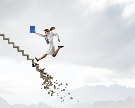 success concept: Young businesswoman walking up collapsing staircase representing success concept