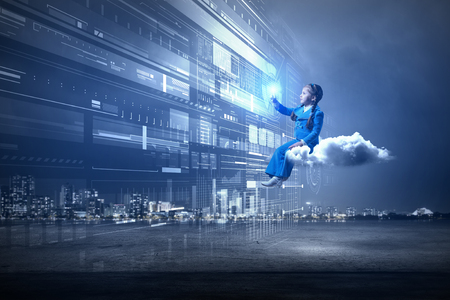 Little girl sitting on cloud and touching virtual panel with finger Banco de Imagens