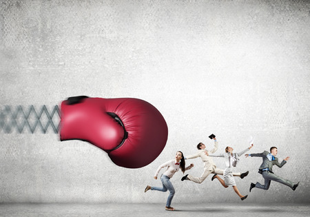 Boxing glove on spring striking group of businesspeople