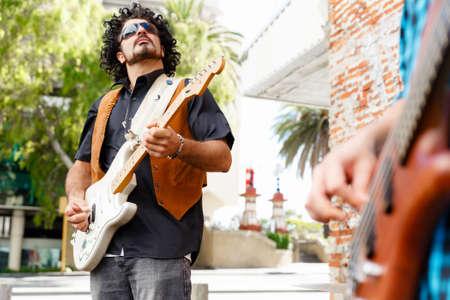 musico: Un músico callejero tocando su guitarra