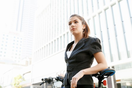 issues: Young woman in business wear commuting on bicycle in city