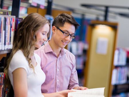 working woman: Two young students working together at the library Stock Photo