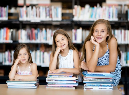 school library: Little girls reading books in library Stock Photo