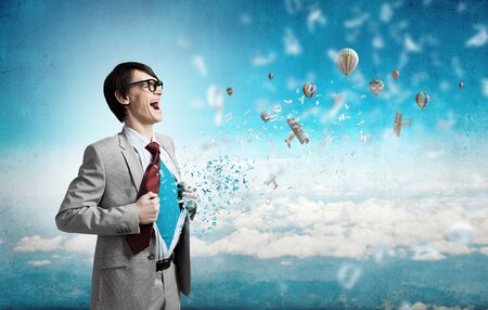 creative force: Young businessman acting like super hero and tearing his shirt off Stock Photo