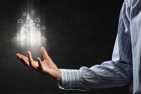 ビジネスマンに手の手のひらに都市モデルを保持している暗い背景 写真素材