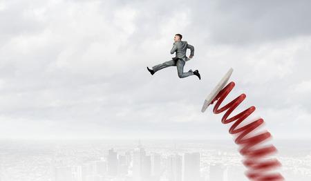 concept: El hombre de negocios que salta en el trampolín como concepto de progreso