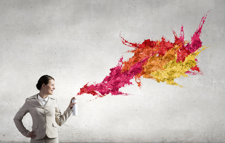 creative idea: Young businesswoman spraying colorful paint from balloon