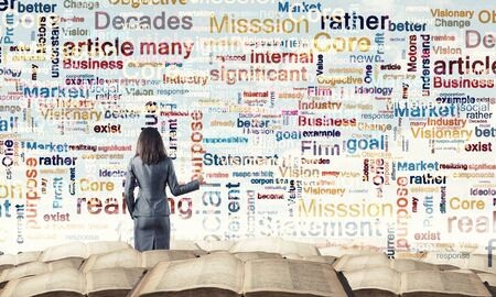 Back view of businesswoman writing leadership concepts on wall