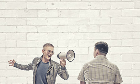 aggressively: Young man in casual screaming aggressively in megaphone on adult man
